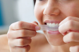 Close up of young woman using a teeth whitening strip